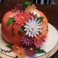 Pumpkin Harvest Cake.... Pumpkin spice cake with cream cheese frosting. Used rice crispies for stem and gumpaste for flowers.