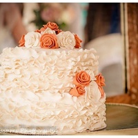 Ivory Ruffled Wedding Cake With Ivory And Coral Spring Roses Ivory ruffled wedding cake with ivory and coral spring roses.