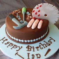 Chocolate Cake Covered With Chocolate Fondant With Fondant Fingers And Tools The Saw Blade Is Made Out Of Gelatin Icing Chocolate cake covered with chocolate fondant, with fondant fingers and tools, the saw blade is made out of gelatin icing.