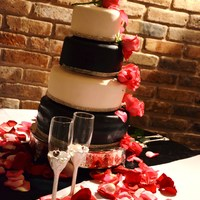 Black And White Wedding Cake With A Small Bit Of Cake Bling Around The Bottom And Pink Roses To Match The Wedding Colors Black and white wedding cake with a small bit of cake bling around the bottom and pink roses to match the wedding colors