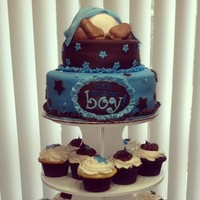 Baby Shower Cupcake Tower With Two Tier Cake On Top Baby shower cupcake tower with two-tier cake on top.