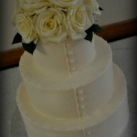 All Buttoned Up 6-9-12 buttercream iced tiers with sugar pearl accents, fondant buttons and fresh ivory roses