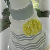"Yellow And Grey Chevron Cake 6-8-10-12-14 buttercream tiers with thin fondant ""pencil"" border and fondant chevrons; fresh hydrangea sprayed yellow (stems..."