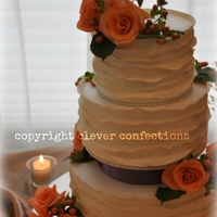 Peach Roses, Berries And Fondant Wrap Wedding Cake 6-8-10 iced in buttercream with very thin fondant strips wrapped around unevenly. Accented with fresh florals, monogram topper, satin and...