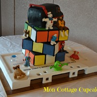 90's Themed Wedding Cake Based on the 80's the main cake is a Rubik's cube and the stand has been hand made using MDF and covered in fondant to look like...