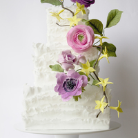 Wedding Cake Paper thin fondant frills adorned with sugar flowers, Ranunculus, Anemones, Roses and Forsythias.