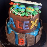 Tmnt Birthday Cake TMNT birthday cake. Buildings around the bottom are made with modeling chocolate, bottom tier is chocolate cake with buttercream icing. Top...