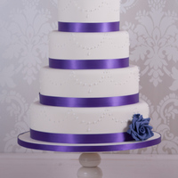Purple Rose Wedding Cake A 4 tier ivory wedding cake decorated with purple satin ribbon, piped pearls and handmade roses.