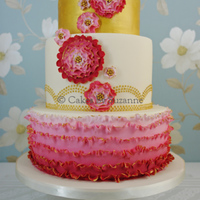 Ombre Ruffles Ombre ruffle cake, with graduating shades of pink/red ruffles accented with edible gold paint on the bottom tier, gold piped dots on the...