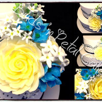 Jasmine gorgeous yellow roses, blue hydrangeas and jasmine on a 2 tier cake with navy piping.