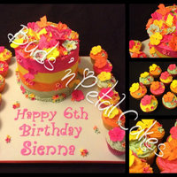 Sienna Brights Rainbow cake with bright buttercream and matching vanilla cupcakes. All topped with fondant flowers and butterflies.