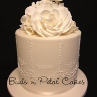 Piped Ivory Ivory extended tier wedding cake with piping and sugar flowers