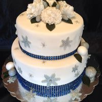 25Th Wedding Anniversary  White cake covered in white fondant. Gum paste roses & mums, snowflakes & accents. Pearl dust snowflakes with pearls finished the...