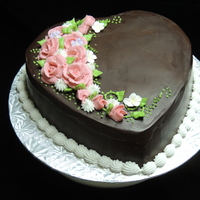 Floral Heart Cake Rich chocolate ganache covered heart cake with a pink floral spray