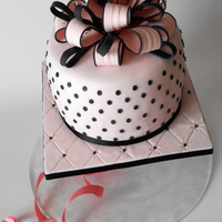 Pink Polka Dot Cake Cake covered in sugar paste soft pink with polka dots blacks and ribbon delicate and elegant.
