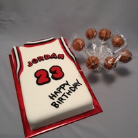 "Basketball Jersey With Basketball Cake Pops Picture of 1/4 sheet cake made to resemble a basketball jersey. Cake is a ""made from scratch"" white cake covered with homemade..."