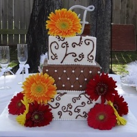 Square Wedding Cake Scroll Designs On Top And Bottom Tiers Quilted Middle Tier Fresh Flowers And Topper Added As Finishing Touches Square wedding cake. Scroll designs on top and bottom tiers. Quilted middle tier. Fresh flowers and topper added as finishing touches.
