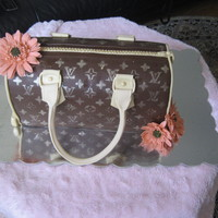 Lv Cake LV Speedy 30. 26 layers of honey cake with sour cream frosting covered in fondant. Flowers are made out of fondant as well.