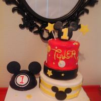Mickey Mouse Theme 1St Birthday Top tier is sitting on a turntable.