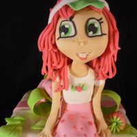 Strawberry Shortcake Strawberry Shortcake modeled in gumpaste on a strawberry cake