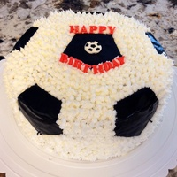 "Buttercream And Fondant Soccer Cake   Used ""grass"" tip for the white buttercream and black fondant."
