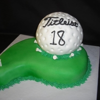 Grooms Titleist Golf Ball Cake Golf ball from ball pan covered in fondant; the green was out of the paisly pan; all accents in fondant and buttercream