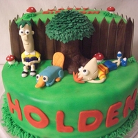Phineas And Ferb Chocolate Cake iced in buttercream and covered in fondant, the tree was madeout of RCT and leaves in buttercream; all characters and other...
