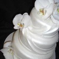 White Orchid Wedding Cake 3 Tier Amaretto Cake with Dulce De Leche Buttercream covered in fondant with fondant drapes; orchids are real. This was my first drape cake...