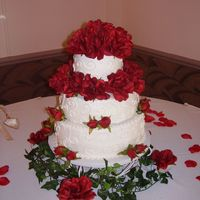 Round Wedding Cake   This is a 6, 10 and 12 inch with red silk roses the bride picked out. Sandy