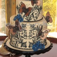 Steampunk Butterflies Cake A bridal shower cake with a steampunk feel, but still feminine with black lace stencil on a tea stain base, shimmery blue rolled roses and...
