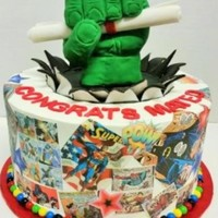 "Comic Book Graduation Cake This is a 10"" cake frosted with Pastry Pride. The hulk's fist is RKT and it is holding a diploma made of gumpaste. The comic book..."