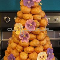 100Th Birthday Croquembouche! Made for a 100th birthday celebration, decorated with her favorite flower. Filled with vanilla bean and chocolate pastry creams, and...