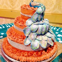 "Peacock Wedding Cake With Chocolate Buttercream  A 14"", 10"", 6"" tiered cake. The peacock was hand molded from rolled fondant. The tail feathers were created by rolling a 1&..."