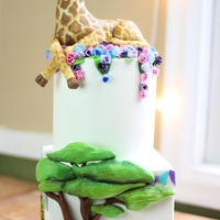 Jungle Theme Baby Shower Cake My take on a jungle themed baby shower cake. Modeling chocolate hand sculpted and painted giraffe on top tier. Tiny wafer paper flowers. A...