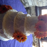Round Wedding Cake Rough textured wedding cake with real flowers. All the tiers are different flavors. Top is lemon cake with apricot filling, white cake with...