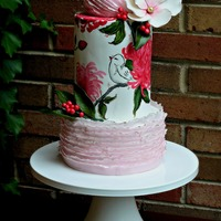 Birds And Blooms Double Barrel hand painted wedding cake with sugar flowers and pink ruffles.