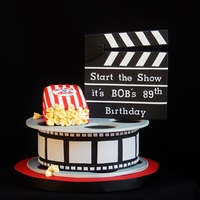 "Movie Reel Reels and clapper board are gumpast fondant mixture. Cake is 8"" round, finished 3"" high, pop corn bag is also cake."
