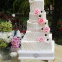 Tall Pleated Cake Mixed shapes 5 tiered pleated cake with gum paste and fantasy flowers cascading down.