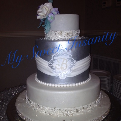 14 10 Double And 6 Covered In Fondant And Pearl And Sugar Encrusted Borders Middle Tier Is Silver With Monogramed Medalian Gumpaste