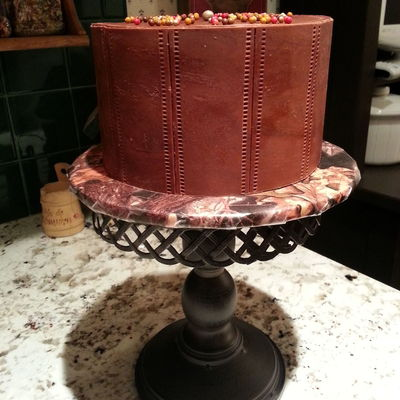 Six Inch Cake Covered With Modeling Chocolate Panels Embossed To Look Like Stitched Leather