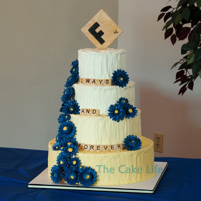 Yellow Ombre Butter Cream Wedding Cake With A Scrabble Theme And Blue Gumpaste Gerber Daisies