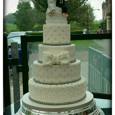 White Wedding Cake With Silver Accents And Bow