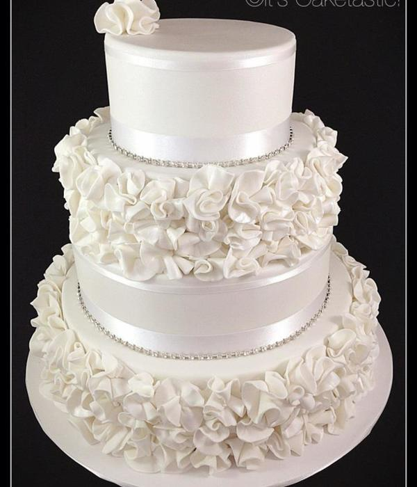 A Four Tier Wedding Cake With Ruffle Flowers Inside There...