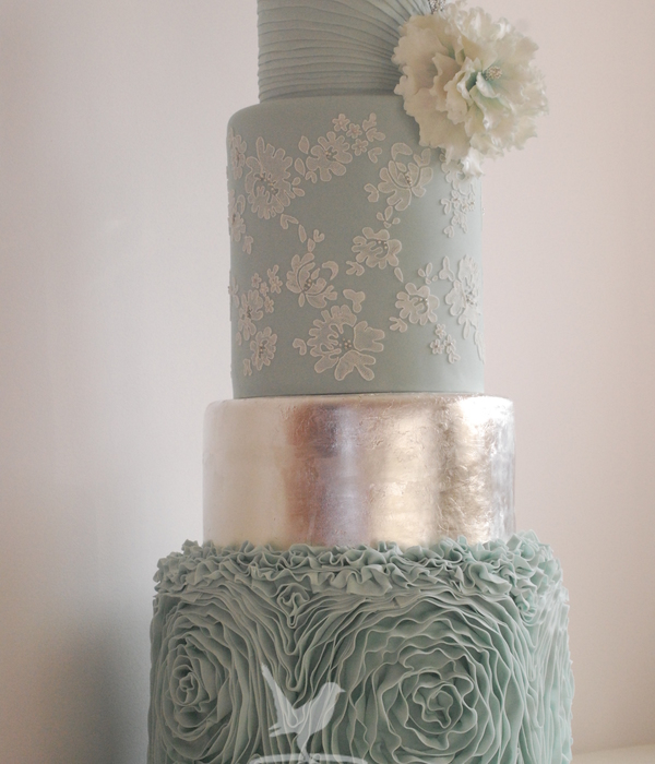 Pale Blue Wedding Cake With Silver Accents Lace Ruffles Silver Leaf And Pleated Top Cake With Fantasy Ruffle Flower