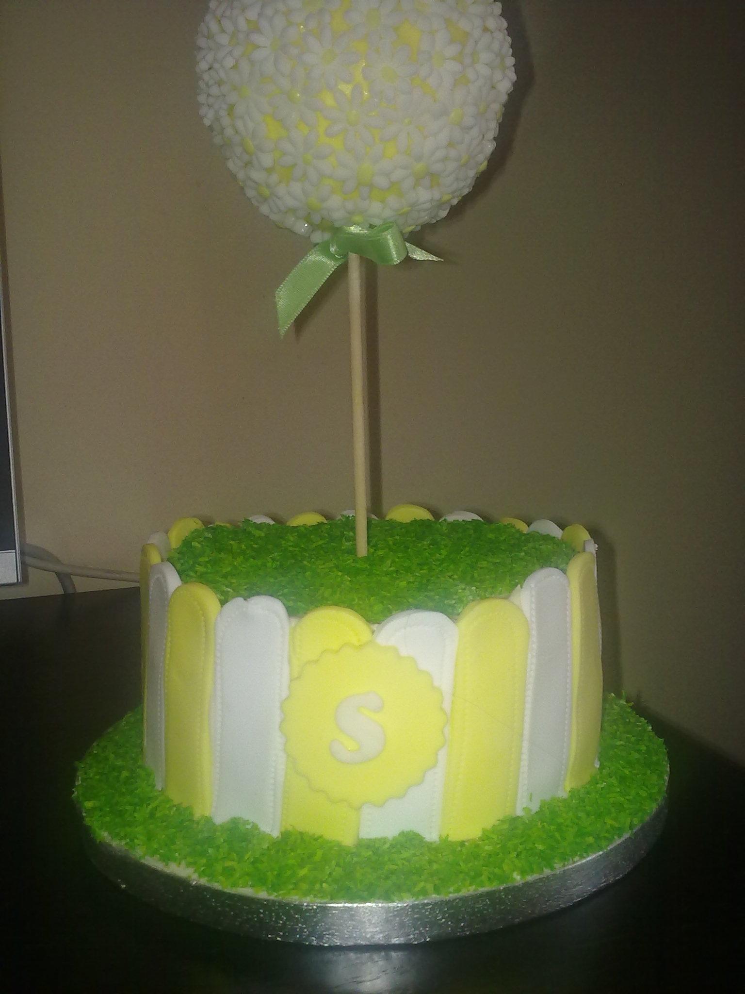 Lemon cake covered in lemon curd buttercream, decorated with fondant.