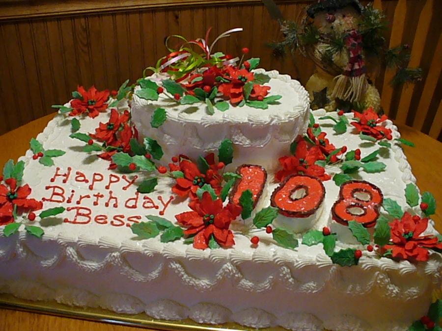 a christmas themed birthday cake for someone turning 108 years old all flowers made of gum paste numbers cut out of cake