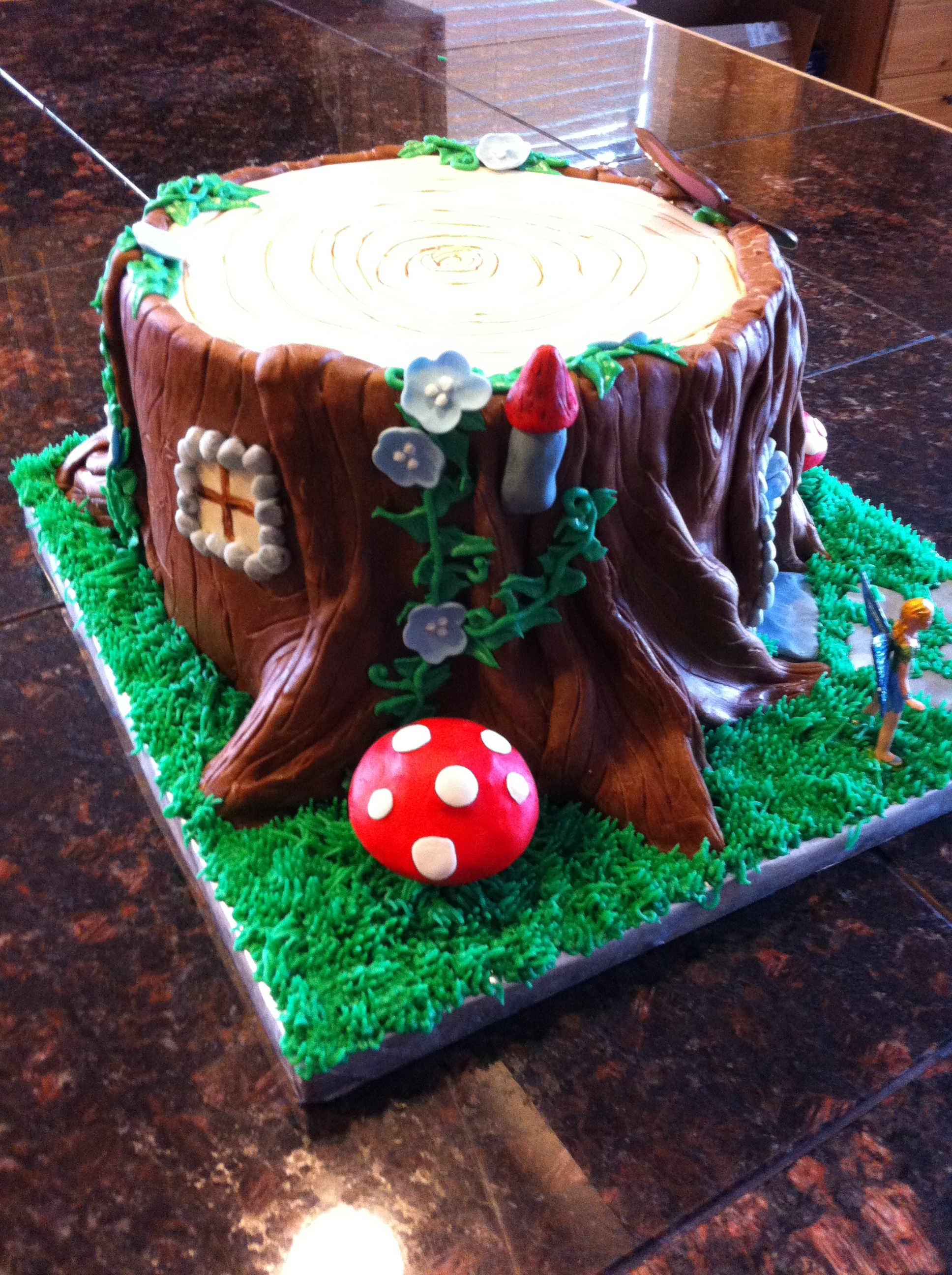 tree stump fairy house for a little girl fondant buttercream grass and vines chocolate butterfly the fairy is not just not that talented