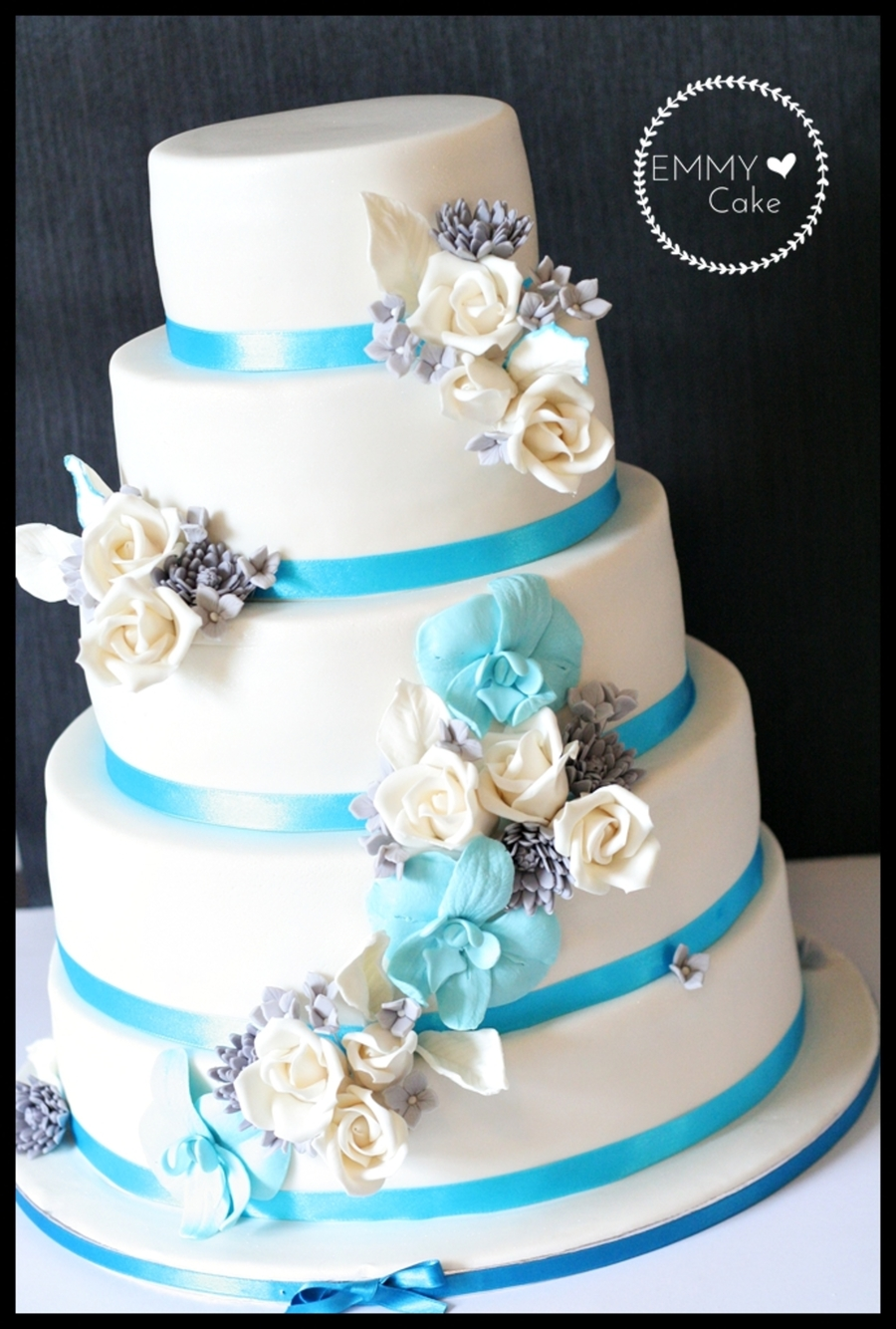 White Wedding Cake With Blue Silver And White Sugar Flowers