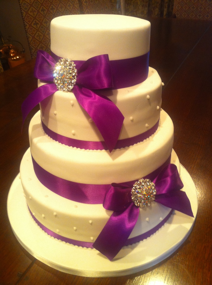 purple ribbon and brooch wedding cake. Black Bedroom Furniture Sets. Home Design Ideas
