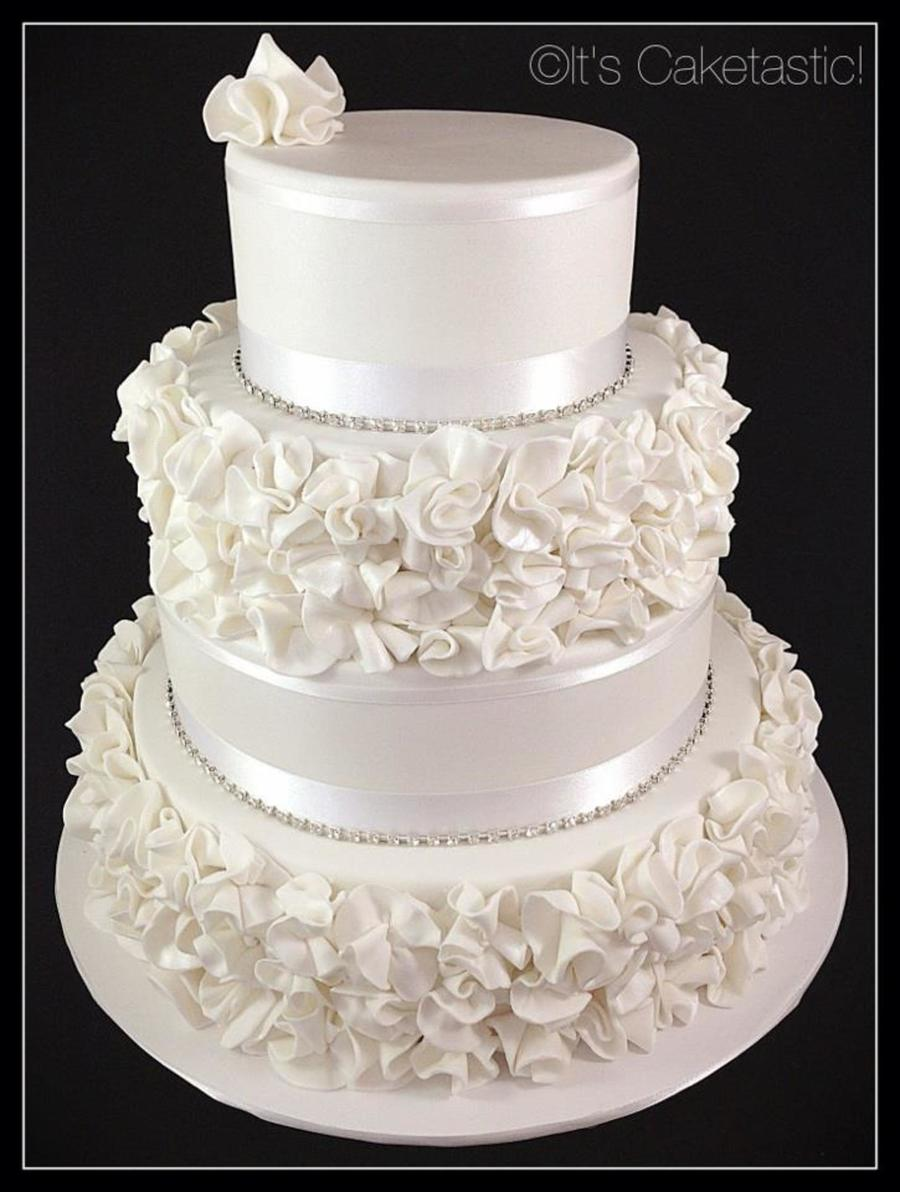 A Four Tier Wedding Cake With Ruffle Flowers Inside There Was Dark ...